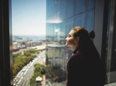 Female graphic designer looking through window