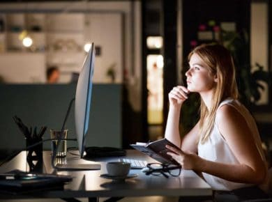 Businesswoman in her office at night working late.